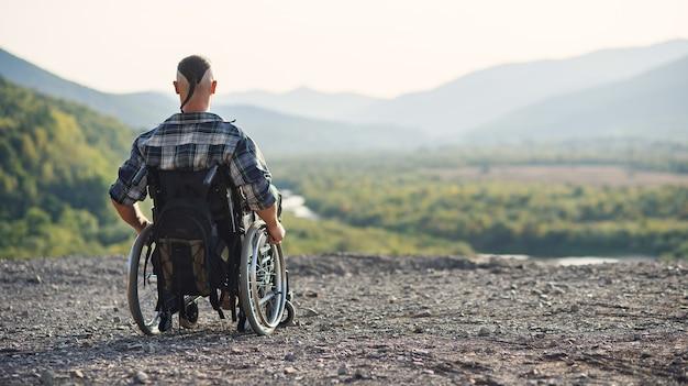 Sportowiec po kontuzji na wózku inwalidzkim cieszy się świeżym powietrzem w górach