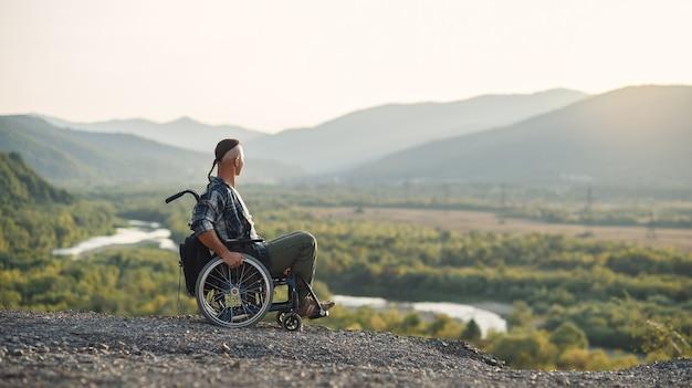 Sportowiec po poważnej kontuzji na wózku inwalidzkim cieszy się świeżym powietrzem w górach. rehabilitacja osób niepełnosprawnych.