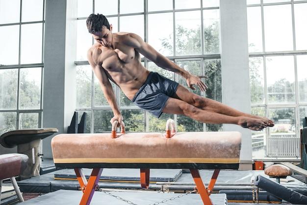Sportowiec podczas trudnych ćwiczeń, gimnastyka sportowa