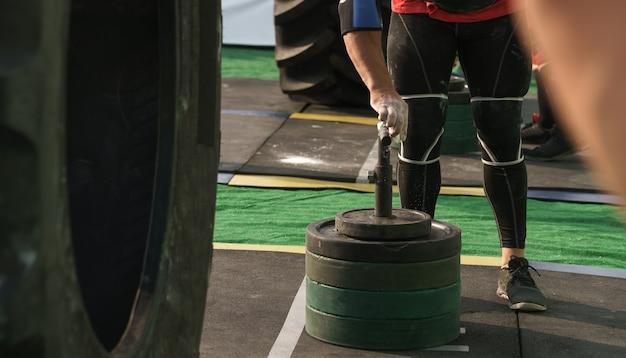 Sportowiec powlekający sztangę proszkową kredą magnezową na zawodach iron man