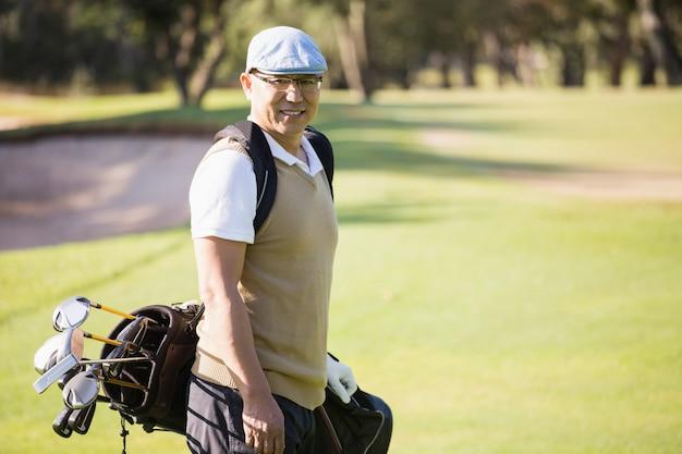 Sportowiec pozuje z jego golfową torbą