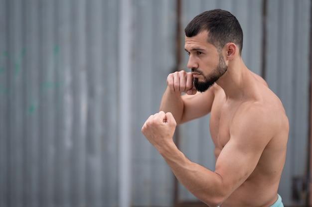 Sportowiec prowadzi walkę z cieniem. bokser trenuje uderzenia pięścią na ulicy