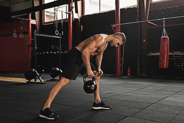Sportowiec robi ćwiczenia z kettlebell na siłowni