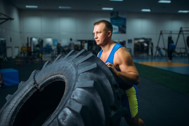 Sportowiec robi ćwiczenia z oponami ciężarówki, crossfit