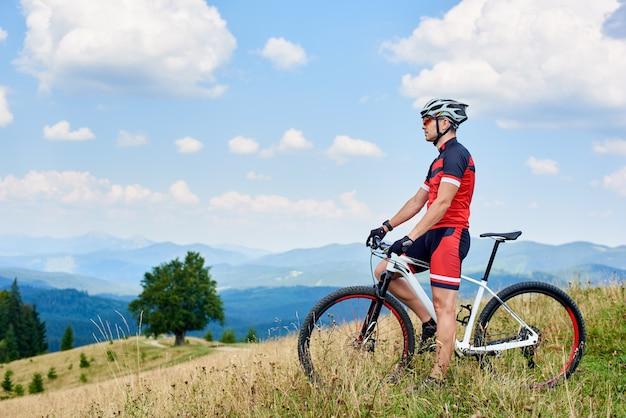 Sportowiec rowerzysta sportowiec stojący z roweru biegowego w trawiastej dolinie w letni dzień, ciesząc się pięknym widokiem na karpaty zdrowy styl życia i koncepcja sportu na świeżym powietrzu