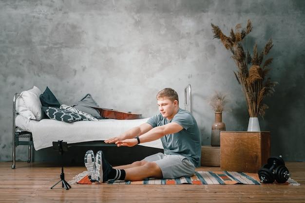 Sportowiec się rozciąga, kręci bloga, ogląda film i portale społecznościowe w sypialni, w tle łóżko, wazon, dywan.