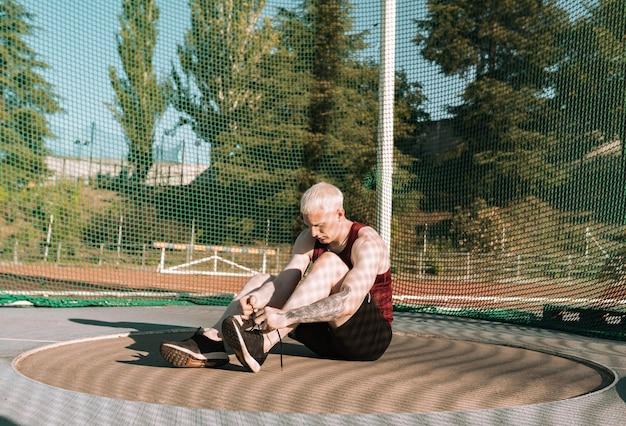 Sportowiec siedzi i wiąże sznurowadła