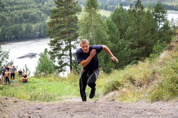 Sportowiec-sportowiec biegnie pod górę w tle górskiej rzeki, gór i lasu. wyścig sprinterski. szybki ruch i efekt biegania, rozmycie