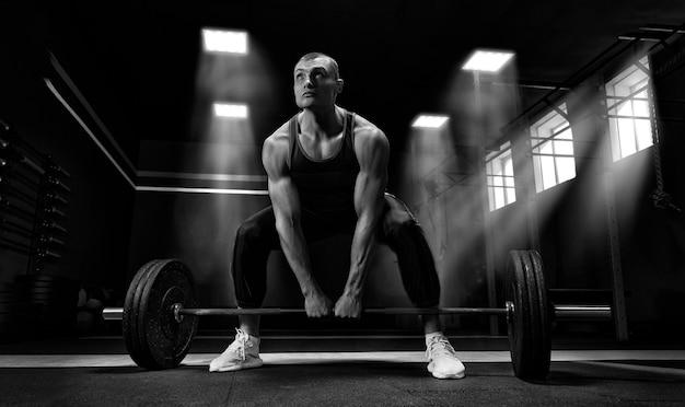 Sportowiec stoi na kolanie w pobliżu baru i przygotowuje się do wykonania martwego ciągu. różne środki przekazu