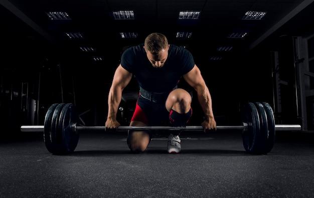 Sportowiec stoi na kolanie w pobliżu drążka na siłowni i przygotowuje się do wykonania martwego ciągu