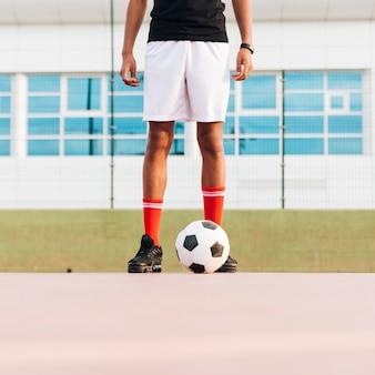 Sportowiec stoi z piłką nożną i przygotowuje się do gry na stadionie