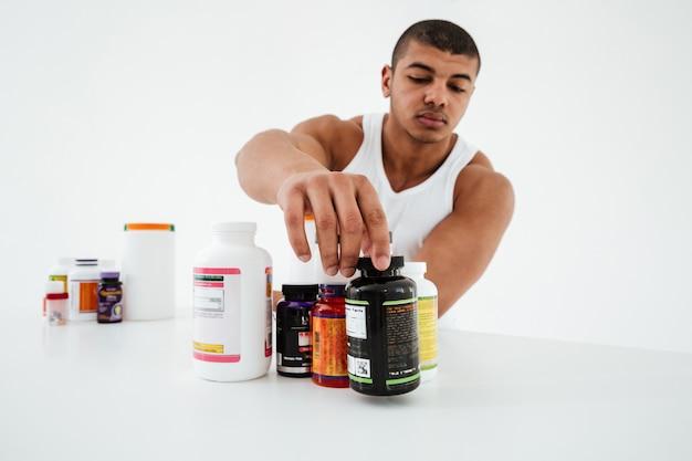 Sportowiec stojący na białej ścianie trzymając witaminy
