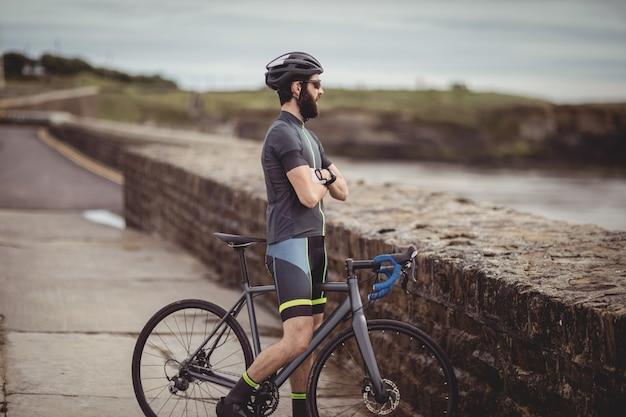 Sportowiec stojący z rowerem