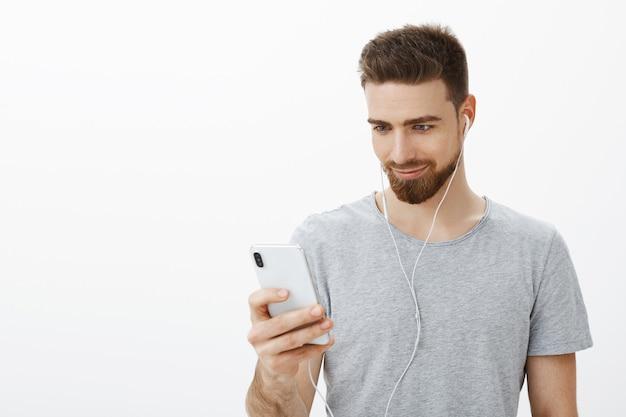 Sportowiec szukający właściwego początku toru treningowego. pewny siebie, przystojny charyzmatyczny brodaty mężczyzna o niebieskich oczach słuchający muzyki w słuchawkach trzymający smartfon, uśmiechając się z radości, patrząc na ekran telefonu komórkowego