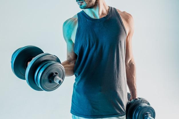 Sportowiec trenujący mięśnie bicepsa z hantlami. brodaty mężczyzna nosi strój sportowy. na białym tle na turkusowym tle. sesja studyjna