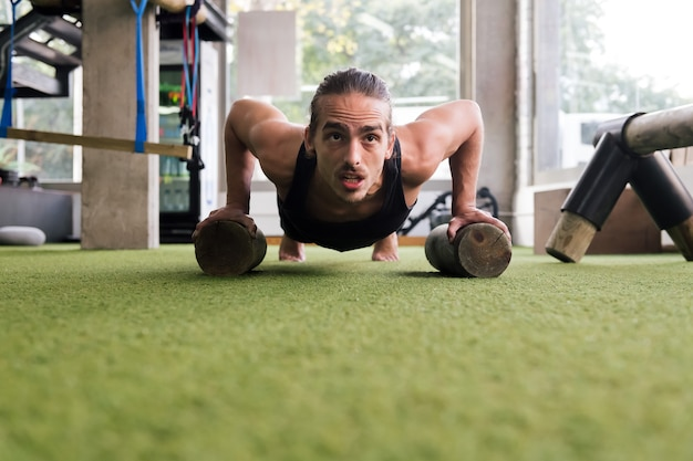Sportowiec trenujący na siłowni robi pompki