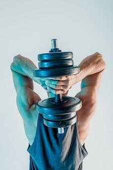 Sportowiec trenujący triceps mięśnie z hantlami. widok człowieka nosić mundur sportowy z tyłu. na białym tle na turkusowym tle. sesja studyjna