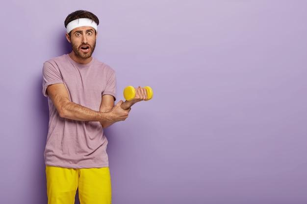 Sportowiec trzyma nadgarstek, podnosi hantle, trenuje mięśnie, odziany w zwykłe ubranie, ma atletyczną sylwetkę