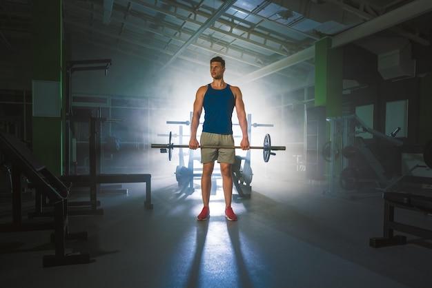 Sportowiec trzyma sztangę w klubie sportowym