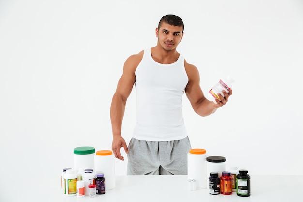 Sportowiec trzyma witaminy i tabletki sportowe.