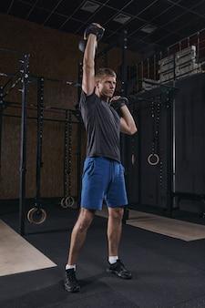 Sportowiec trzymający kettlebell ćwiczący na siłowni