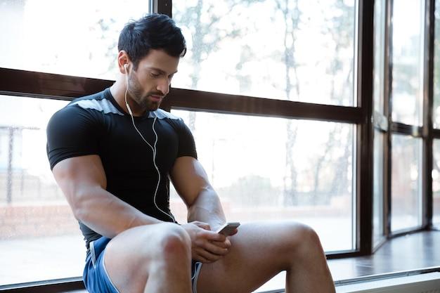 Sportowiec ubrany w niebieskie spodenki i czarną koszulkę, słuchający muzyki, używający telefonu komórkowego siedzącego na parapecie