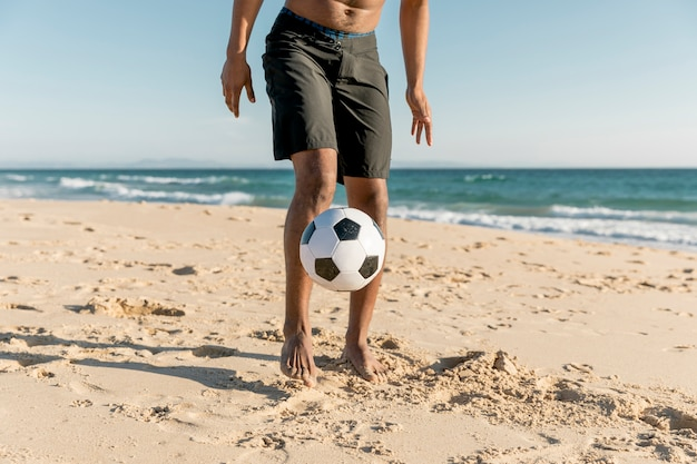 Sportowiec uderza piłkę na wybrzeżu