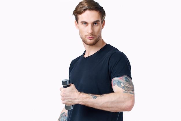 Sportowiec w czarnej koszulce z hantlami na białym tle widok z boku
