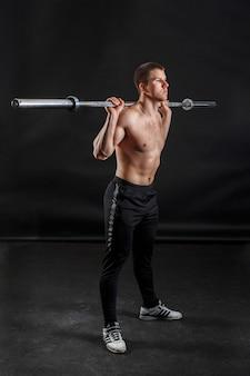 Sportowiec w czarnej trykotie fitness stojący i trzymający sztangę na ramionach