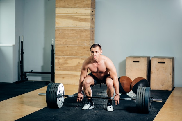 Sportowiec w czarnych szortach podnoszących duży sztangę