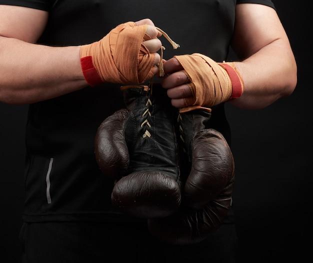 Sportowiec w czarnym mundurze trzyma w ręku bardzo stare brązowe rękawice bokserskie