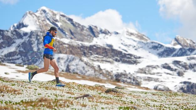 Sportowiec w górach z kijami