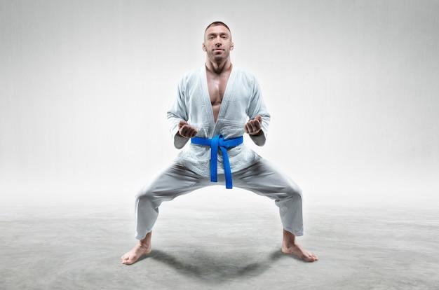 Sportowiec w kimono z niebieskim pasem stoi w pozycji bojowej. koncepcja karate, sambo, jujitsu. różne środki przekazu