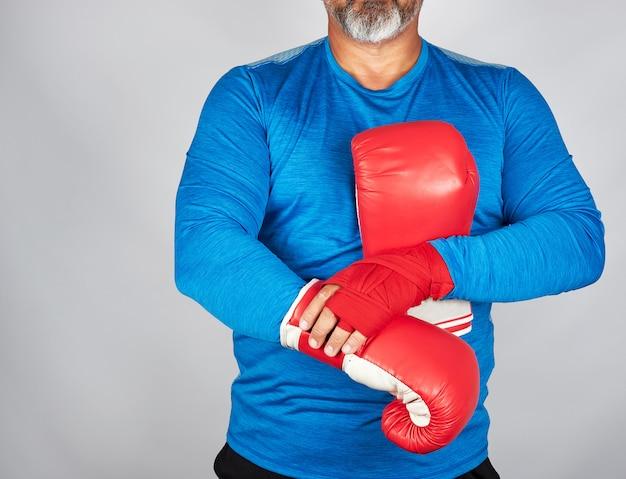 Sportowiec w niebieskich ubraniach, ręce są przewijane czerwonym bandażem