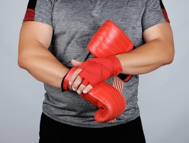 Sportowiec w niebieskich ubraniach, ręce zwinięte w czerwony tekstylny bandaż