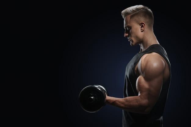 Sportowiec w treningu pompowania mięśni z hantlami. silny kulturysta o doskonałych mięśniach naramiennych, barkach, bicepsach, tricepsach i klatce piersiowej. zbliżenie: mężczyzna fitness moc.