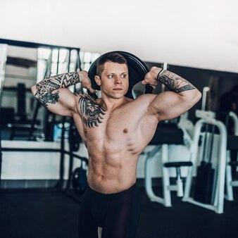 Sportowiec w treningu pompuje mięśnie pleców i ramion