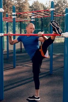 Sportowiec wykonujący ćwiczenia rozciągające trening na boisku sportowym