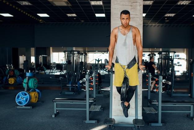 Sportowiec wykonujący pompki na nierównych drążkach na siłowni
