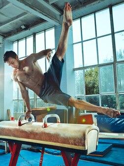 Sportowiec wykonujący trudne ćwiczenia gimnastyczne na siłowni ćwiczenie sportowe