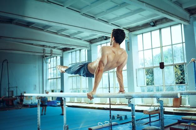 Sportowiec wykonujący trudne ćwiczenia gimnastyczne na siłowni gimnastyczka gimnastyczna