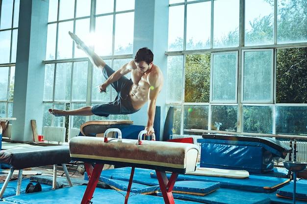 Sportowiec wykonujący trudne ćwiczenia gimnastyczne na siłowni. sport, ćwiczenia, gimnastyczka, zdrowie, trening, koncepcja sportowca. kaukaski dopasowany model