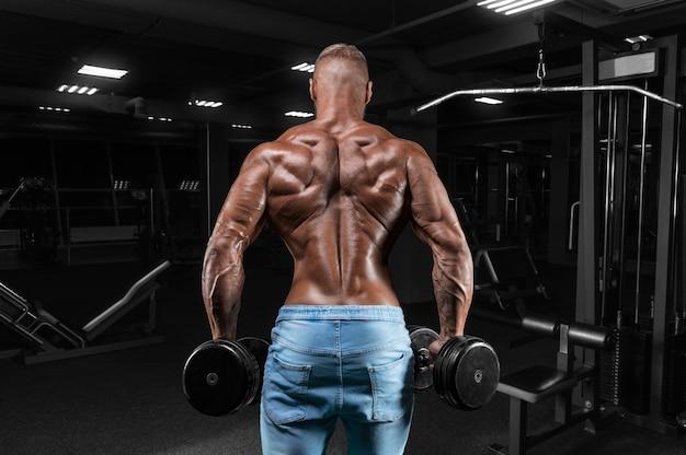 Sportowiec wykonuje ćwiczenia na siłowni z hantlami. widok z tyłu.