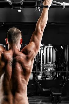 Sportowiec wykonuje podciągnięcia - broda na siłowni, model ze sportowym body topless
