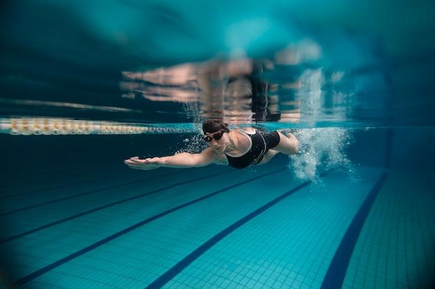 Sportowiec z goglami pływający pod wodą w pełnym ujęciu