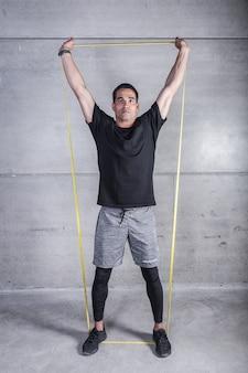Sportowiec z gumką trzymającą ręce podniesione