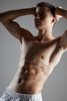 Sportowiec z kostkami na brzuchu trzyma ręce za głową