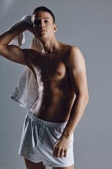 Sportowiec z nadmuchanym tułowiem trzymający ręcznik na ramieniu przycięty widok