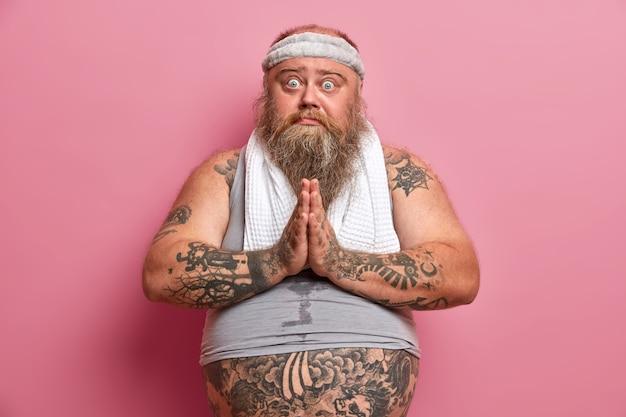 Sportowiec z nadwagą naciska dłonie i błaga kanapę o mały odpoczynek, czuje się zmęczony treningiem, nosi niewymiarową kamizelkę, opaskę i ręcznik na szyi, ma tatuaże, wygląda z błagalnym wyrazem