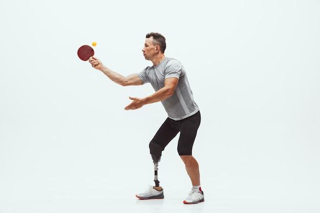 Sportowiec z niepełnosprawnością lub osoba po amputacji na białym tle na białej ścianie